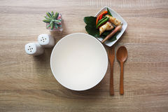 Empty bowl for text input or food and have spoon, forks and have side dishes. Are placed on a brown wooden table Royalty Free Stock Image
