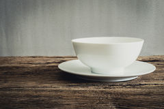 Empty bowl and white plate on wooden tabletop Stock Image