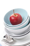 Empty bowls, plates and red apple, close-up, isolated Stock Images