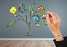 Hand holding pen and Drawing of Business graphics on plant branches on wall Stock Image