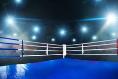 Empty boxing ring, view on corner with white ropes. Empty boxing ring, blue flooring, view on corner with white ropes. Professional arena for sport competitions royalty free stock photo