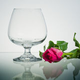Empty Brandy glass and pink rose on glass Royalty Free Stock Images