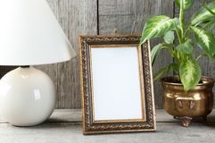 Empty brass picture frame on wooden background. Empty brass vertical picture frame, green plants and table lamp on old wooden gray textured background. Home stock images