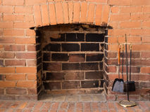 Empty Brick Fireplace with Fire Tending Equipment Royalty Free Stock Images