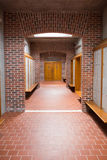 Empty brick walled corridor with tiled flooring in college Royalty Free Stock Photography