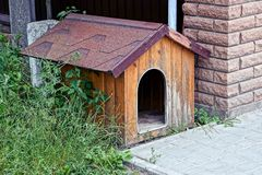Empty brown dog house near a brick wall in the grass royalty free stock photo