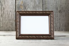 Empty picture frame on wooden background. stock photos