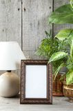 Empty brown picture frame on wooden background. royalty free stock images