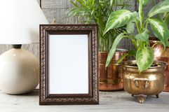 Empty brown picture frame on wooden background. Empty brown vertical picture frame, green plants and table lamp on old wooden gray textured background. Home stock images