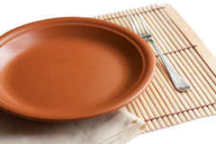 Empty brown plate and fork. Linen napkin under the dish Stock Photos