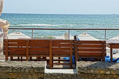 Brown wooden bench against the blue sky and sea waves royalty free stock photo