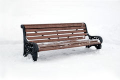 Empty brown wooden bench outdoor in winter. Empty brown wooden bench outdoor in a park in winter side view closeup Stock Photos