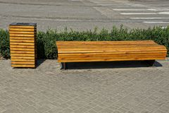 A brown wooden bench and an urn stand on the sidewalk on a city street royalty free stock images