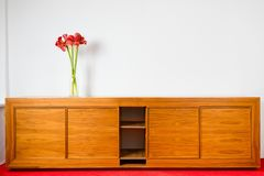 Empty brown wooden commode with three flowers on red car carped and next to white wall royalty free stock photos