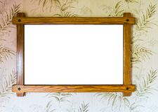 Empty brown wooden picture frame hanging on a wall with decorated wallpaper background. A empty brown wooden picture frame hanging on a wall with decorated royalty free stock images