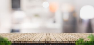Empty brown wooden plank table top with blurred home kitchen wit royalty free stock image