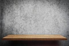 Empty brown wooden shelf on gray wall. Empty brown wooden shelf on gray cement wall Stock Photography