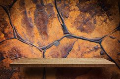 Empty brown wooden shelf on orange rock background. Empty brown wooden shelf on orange rock wall background Royalty Free Stock Photography