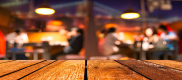 Empty brown wooden table and  Coffee shop blur background with bokeh image Royalty Free Stock Photo