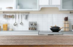 Empty brown wooden table in modern kitchen. Mockup for design stock photo