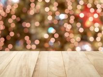 close up empty brown wooden table top with defocused small colorful lights bokeh on Christmas tree background royalty free stock photo