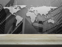 Empty brown wooden table top over black and white world map with. Financial graph and city tower, Elements of this image furnished by NASA Stock Images