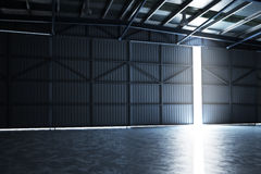 Empty building hanger with the door cracked open with room for text or copy space. Stock Photography
