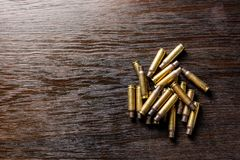Empty bullet casings on a dark, wooden table royalty free stock photos