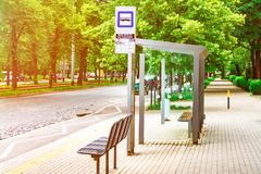 An empty bus stop in the center of the city is lit by the sun, a stop against the background of green trees stock photography