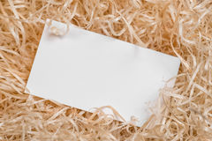 Empty business card as a placeholder for shipping text on raffia pile. Stock Photos