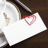Empty business card and heart shaped paper clip Royalty Free Stock Photos