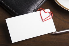 Empty business card and heart shaped paper clip Stock Photo