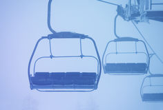 Empty cabins of chairlift on ropeway in thick fog Royalty Free Stock Photos