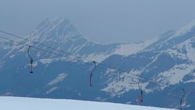 Empty cableway on windy snowy mountain range, storm warning, avalanche hazard stock footage