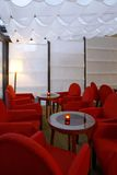 Empty Cafe. Empty interior of a cafe with plush red chairs around small tables with a burning candle on each table stock photos