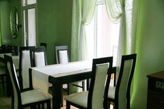 Empty cafe. With a table and chairs illuminated with light from a window Stock Images