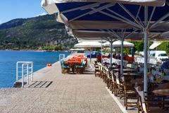 Empty cafe on a coastline. Empty cafe on a coastline of one of the Greek islands early in the morning on a sunny day stock photo