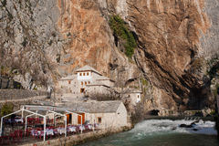 Empty cafe near the fast mountain river & ancient Sufi monastery Blagaj Tekke above Royalty Free Stock Photo