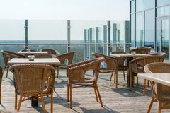 Empty cafe with rattan wicker armchairs and tables on summer garden terrace outdoor, free space. Table and chairs in empty cafe. royalty free stock images