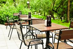 Empty woode tables and chairs in the outdoor cafe ready for visitors. royalty free stock photos