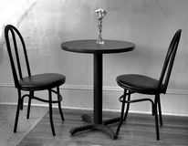 Empty cafe table. Small cafe table with two empty chairs , sunlight streams in from the left, small vase of flowers sits on table, black and white Stock Photos