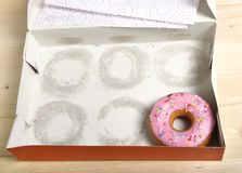 Empty cakes box with only one tempting and delicious donut with toppings left Royalty Free Stock Photos