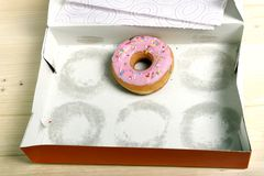 Empty cakes box with only one tempting and delicious donut with toppings left Stock Photography