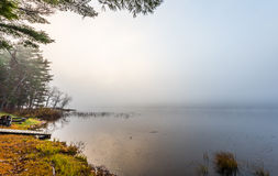 Empty campfire in early morning fog on a lake near Ottawa, Ontario. Stock Images