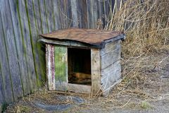 An empty canine box near the fence. Wooden doghouse in a dry grass near a wooden fence Royalty Free Stock Image