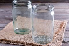 Empty canning jars await use on a wooden table Royalty Free Stock Photo