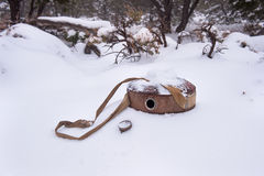 Empty canteen. An empty vintage hiking and camping canteen lying in the snow in a remote part of the desert during a snowy winter royalty free stock image