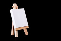 Empty canvas on easel on a black background Royalty Free Stock Images