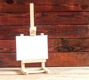Easel with blank canvas on wooden table. Empty canvas on easel on old wooden background Royalty Free Stock Image
