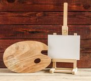 Easel with blank canvas on wooden table. Empty canvas on easel on old wooden background Stock Photos